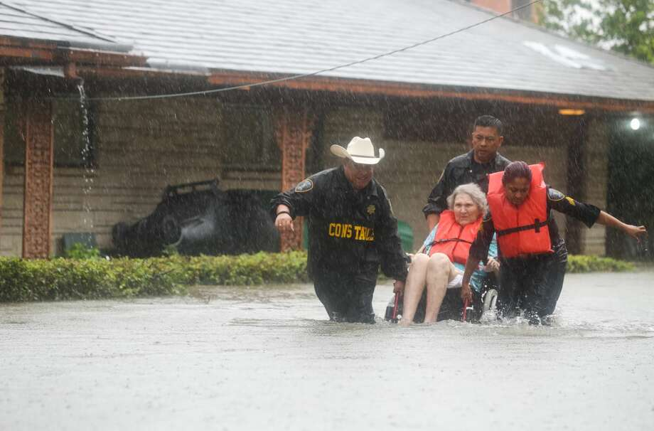 Precinct 6 Deputy Constables Sgt. Paul Fernandez, from left, Sgt. Michael Tran and Sgt. Radha Patel rescue an elderly woman from rising water on North MacGregor Way, near Brays Bayou, after heavy rains from the remnants of Hurricane Harvey, Saturday, August 27, 2017, in Houston. ( Jon Shapley / Houston Chronicle ) Photo: Jon Shapley