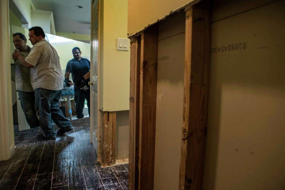 Edwin Cerritos, left, and Louis Cerritos carry a mirror from a Meyerland area home, that was flooded in the aftermath of Hurricane Harvey, as they continue restoration work on Thursday, Sept. 21, 2017, in Houston. The house had been newly renovated and is now being gutted by Legal Eagle Contractors.