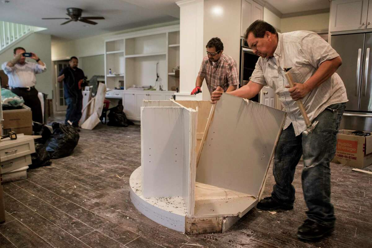 Edwin Cerritos, right, and Oscar Cerritos tear apart a kitchen island during restoration work of a Meyerland area home, that was flooded in the aftermath of Hurricane Harvey, on Thursday, Sept. 21, 2017, in Houston. The house had been newly renovated and is now being gutted by Legal Eagle Contractors.