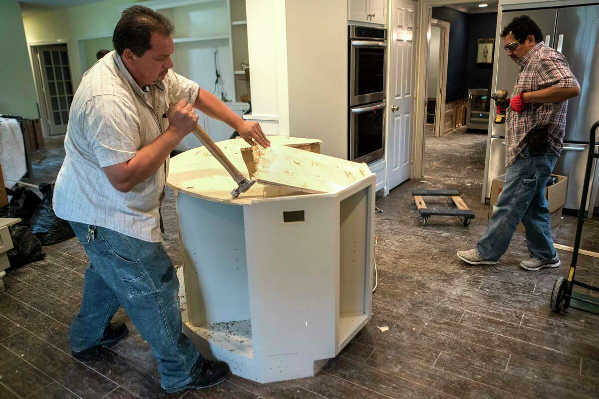 Edwin Cerritos, left, and Oscar Cerritos tear apart a kitchen island during restoration work of a Meyerland area home, that was flooded in the aftermath of Hurricane Harvey, on Thursday, Sept. 21, 2017, in Houston. The house had been newly renovated and is now being gutted by Legal Eagle Contractors.