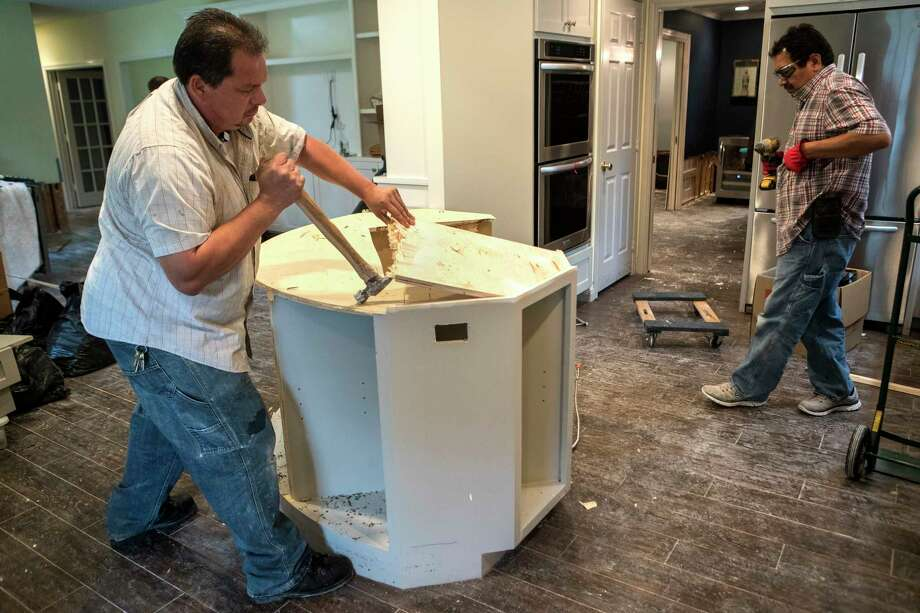 Edwin Cerritos, left, and Oscar Cerritos tear apart a kitchen island during restoration work of a Meyerland area home, that was flooded in the aftermath of Hurricane Harvey, on Thursday, Sept. 21, 2017, in Houston. The house had been newly renovated and is now being gutted by Legal Eagle Contractors. Photo: Brett Coomer, Houston Chronicle / © 2017 Houston Chronicle