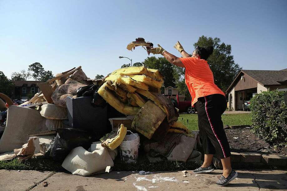 Regina Perry throws out wet drywall as she cleans out her Houston home that was inundated with floodwaters from Harvey. Photo: Joe Raedle, Getty Images / 2017 Getty Images
