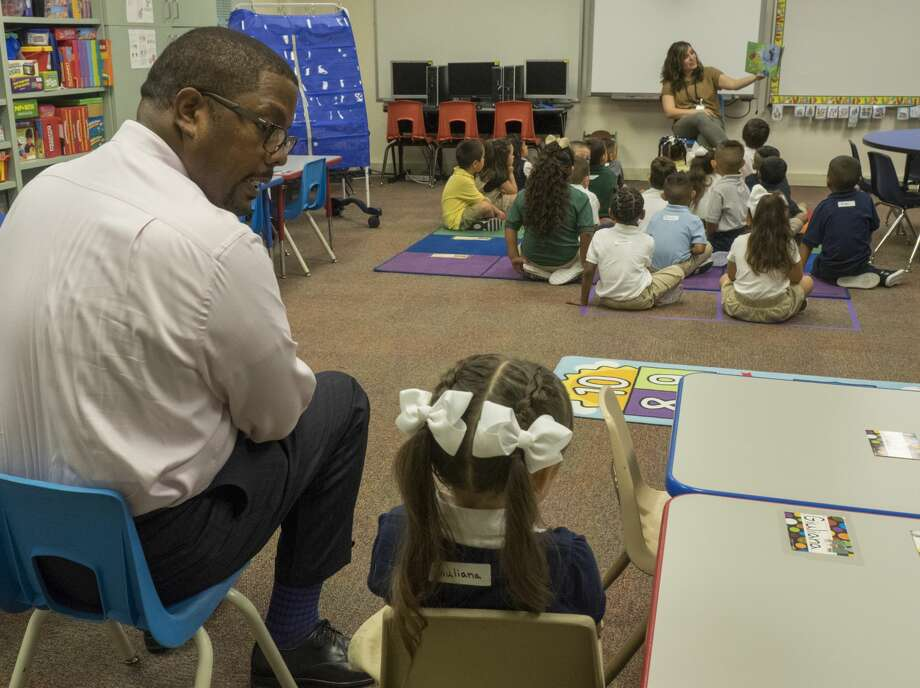 Midland ISD Superintendent Orlando Riddick sits with a South Elementary School pre-k student who was a little shy about joining her classmates on the first day of school. Photo: Tim Fischer/Midland Reporter-Telegram