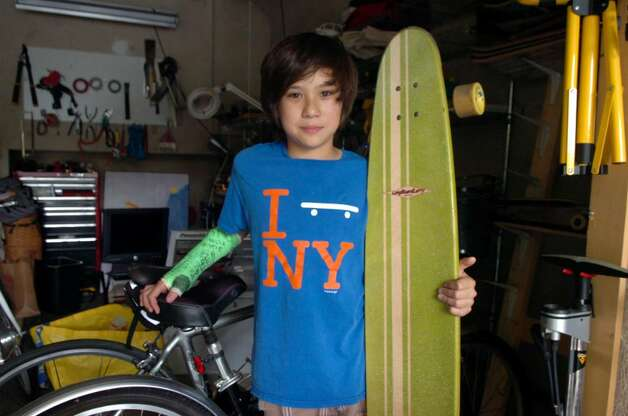 Sebastian Oe, 12, holding his board standing in his family garage on Tuesday, June 22, 2010. After Sebastian fractured his arm twice in the same place in skateboarding and snowboarding falls last year, a doctor found low levels of vitamin D in his blood, a contributing factor to the breaks. Local doctors and nutritionists are seeing many people, both children and adults, deficient in a vitamin that, aside from creating stronger bones, may be associated with reduced risks of some cancers and other ailments. Photo: Helen Neafsey / Greenwich Time
