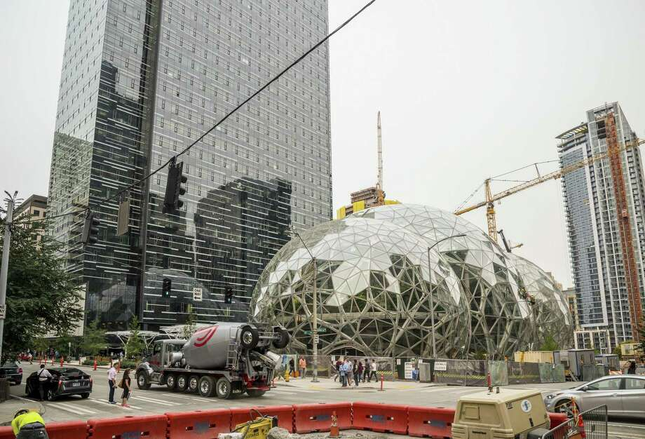 A recently built trio of geodesic domes is an addition to Amazon's Seattle headquarters building. Amazon has put out a request for cities to bid on a second headquarters. However, high-tech cities have discovered that much of what Amazon is demanding by way of amenities and infrastructure aren't possible without a city's commitment to social equity. Photo: Stuart Isett /New York Times / NYTNS