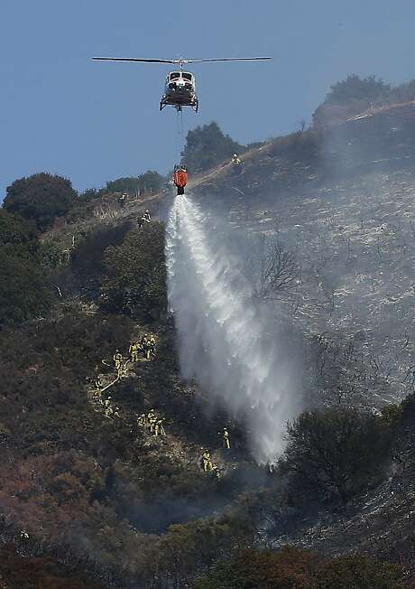 A helicopter drops water over a part of the Oakland hills. Photo: Jeff Chiu, Associated Press