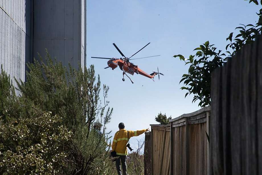 A helicopter drops water on an hillside of dry brush and grass as it threatened homes and caused evacuations on Tuesday, Sept. 26, 2017 in Oakland, Calif. Photo: Paul Kuroda, Special To The Chronicle