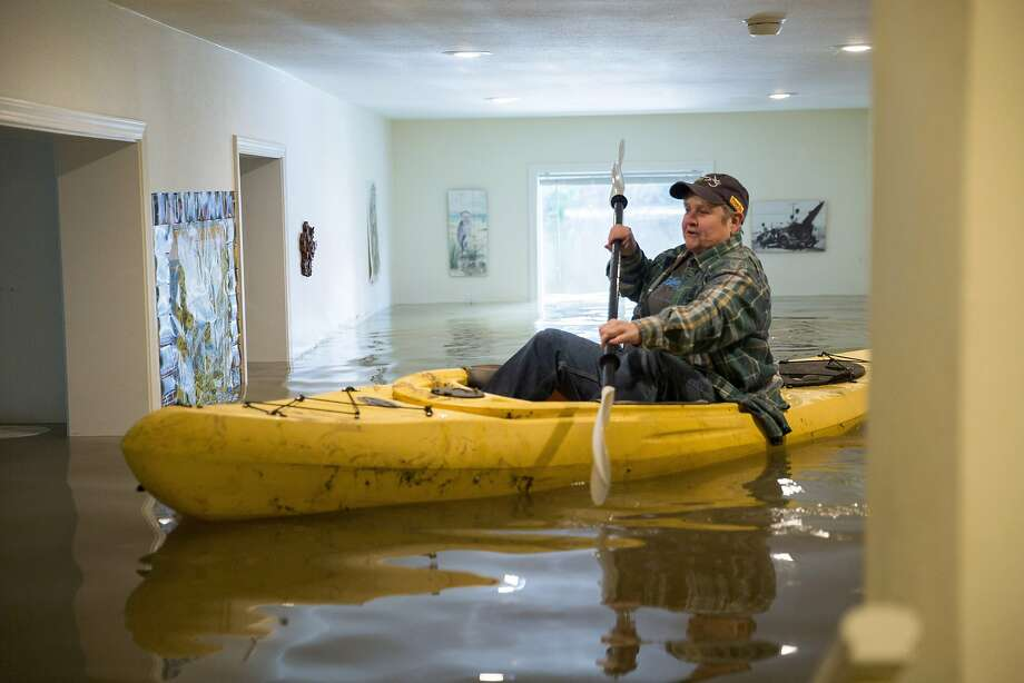 Lorin Doeleman used a kayak to check her mother's flooded home in Guerneville in January amid days of flooding from the winter rains. Photo: Santiago Mejia, The Chronicle