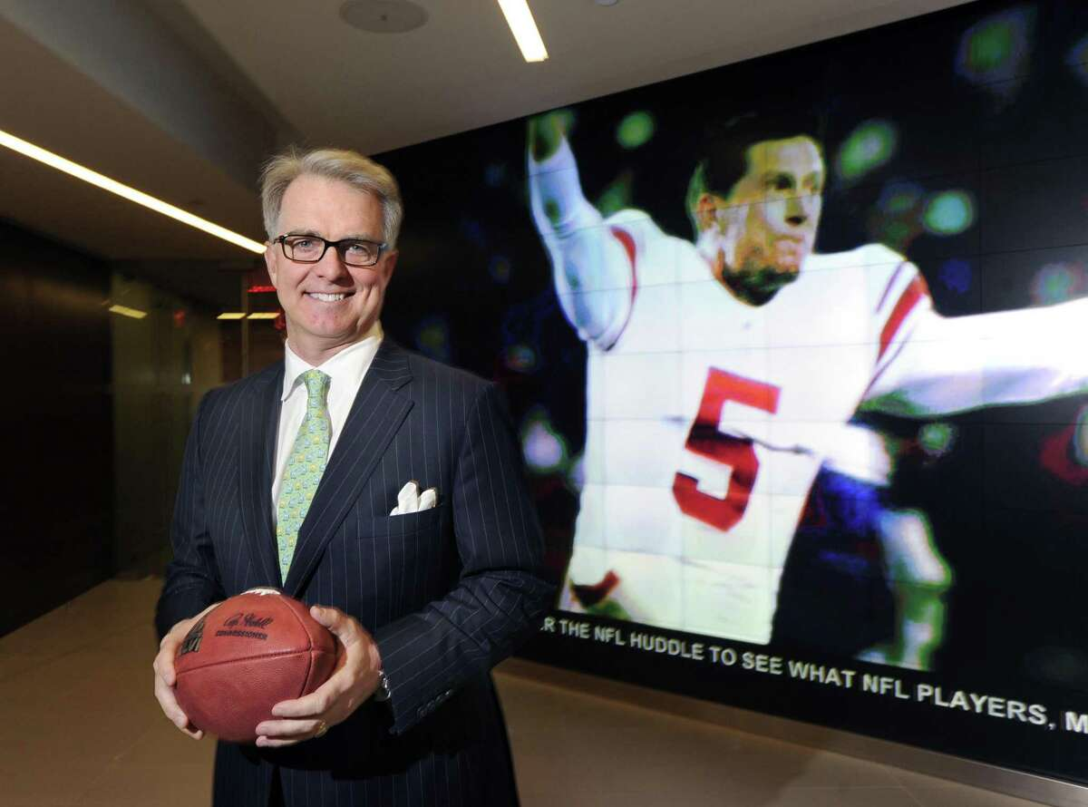 Greenwich resident Paul Hicks III, executive vice president of communications and government affairs for the National Football League at the time, in front of a large video screen image of New York Giants punter and placeholder Steve Weatherford reacting to the Giants game-winning field goal against the 49ers that sent the team to this year's Super Bowl, in the lobby of the NFL offices in New York City, Tuesday afternoon, Jan. 31, 2012.