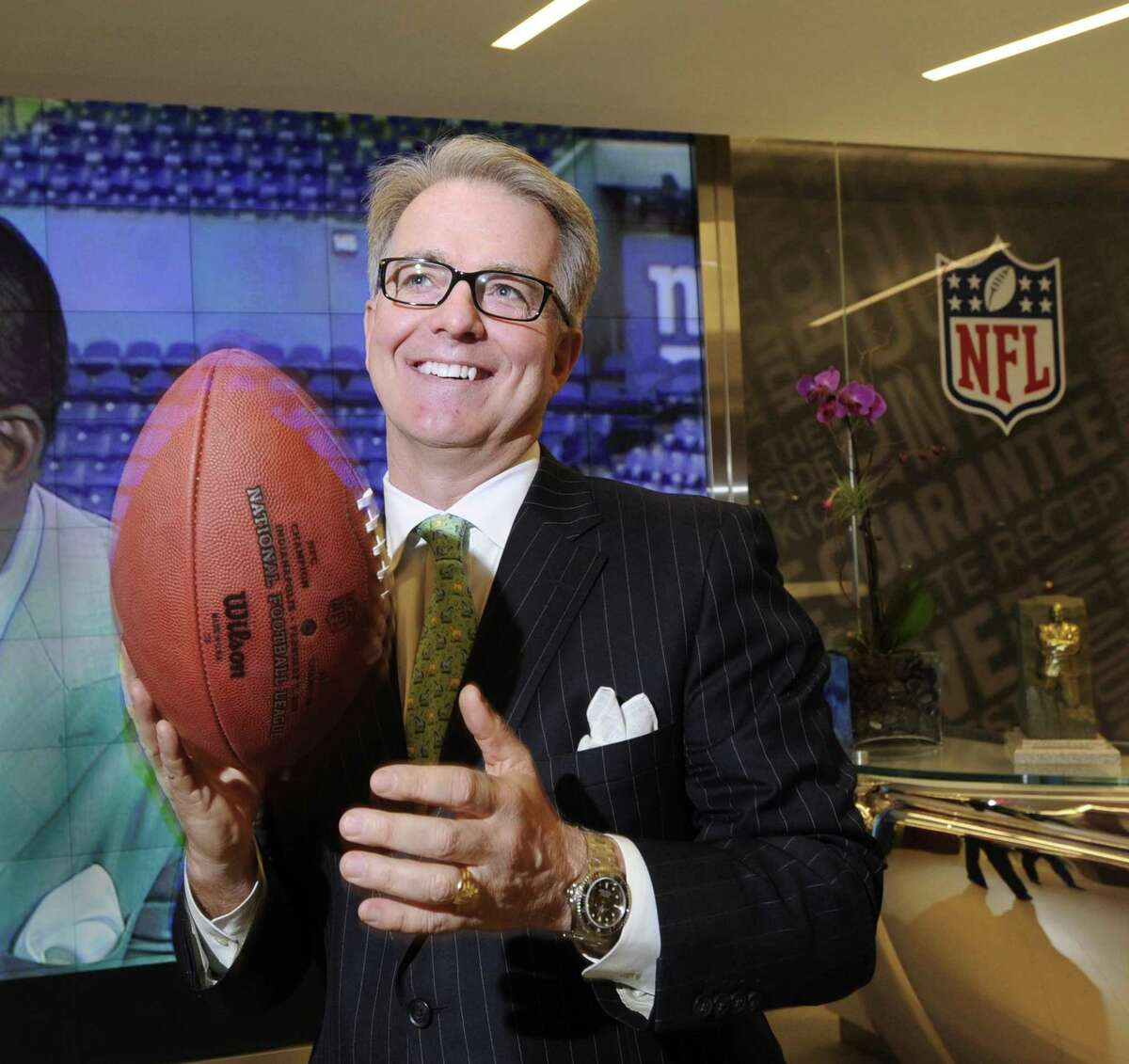 Greenwich resident Paul Hicks III, executive vice president of communications and government affairs for the National Football League at the time, holds a football in the NFL offices in New York City, Tuesday afternoon, Jan. 31, 2012.