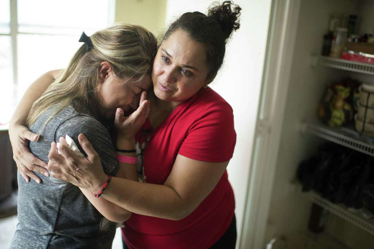 A neighbor consoles Ruby Rodriguez in her water-damaged house in Houston on Sept. 3. Rodriguez fled the rapidly flooding house clutching a briefcase containing all the paperwork for her daughter's DACA application. MUST CREDIT: Photo by Michael Robinson Chavez for The Washington Post.