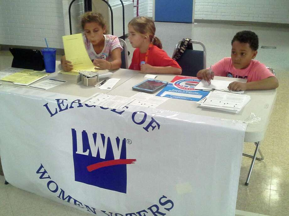 Hhelping the league of women voters with their voter registration efforts at the Boys and Girls Club of Greenwich are club members from left, 9-year-old Ashley Mariscal, 8-year-old Dominika Jakab and 9-year-old Deion Rossi. Photo: Ken Borsuk