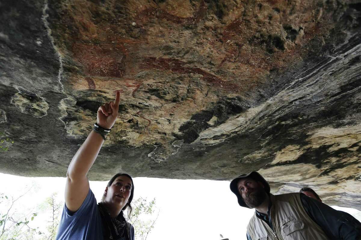 Archaeologists Amanda Castañeda (left) and Jerod Roberts study a cave painting located on a private ranch in Val Verde County. The artwork that dot the Lower Pecos region date back 1,000 to 4,200 years.