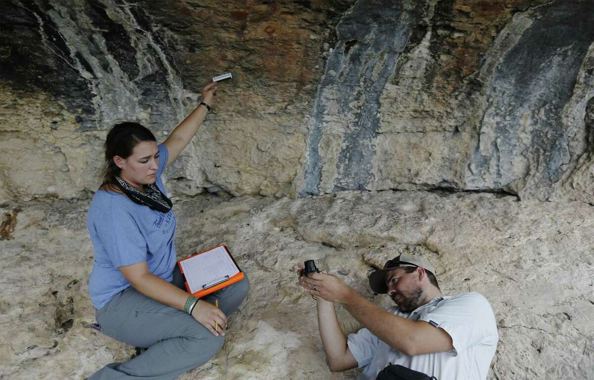 Archaeologists Amanda Castañeda (left) and Charles Koenig record measurements from a cave painting near Comstock, Texas. The archaeologists use equipment to record the artwork using high-resolution camera equipment and take extensive notes about the work created on the limestone caves by indigenous people. The plan is for data collected to be available for other researchers to study.