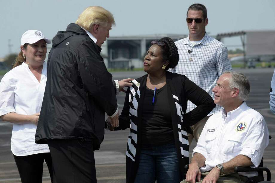 President Donald Trump talks with Rep. Sheila Jackson Lee, D-Texas, and Texas Gov. Greg Abbott before boarding Air Force One at Ellington Field after meeting people affected by Hurricane Harvey during a visit to Houston on Sept. 2. Lee crossed words with Trump Monday and Tuesday about the president's attack on NFL players who take a knee during the national anthem. Photo: Susan Walsh /Associated Press / Copyright 2017 The Associated Press. All rights reserved.