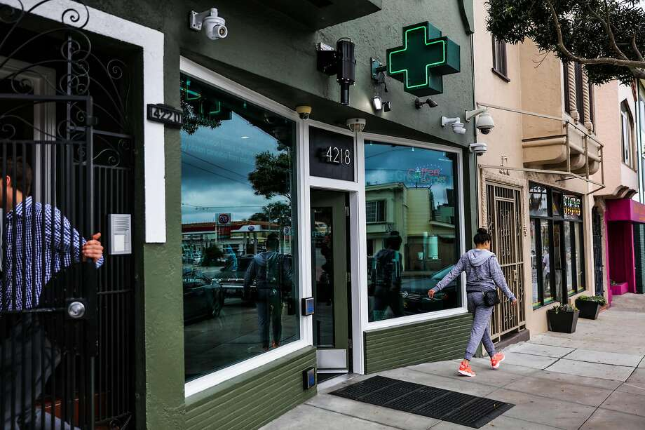 "People walk by the Green Cross cannabis dispensary in  the Outer Mission. Rules being considered could restrict pot shops to a few tiny ""green zones."" Photo: Gabrielle Lurie, The Chronicle"