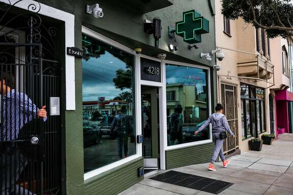People walk by the exterior of cannabis dispensary, The Green Cross, in San Francisco, California, on Friday, Oct. 28, 2016.