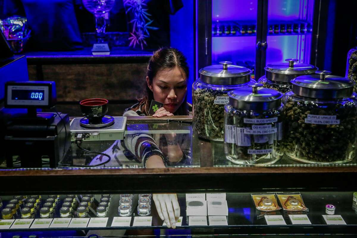 Manager Natalie Tran organizes the display case, at cannabis dispensary The Green Cross, in San Francisco, California, on Tuesday, Nov. 1, 2016.