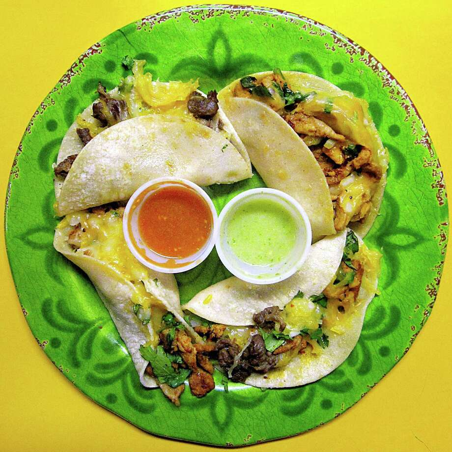 Four mini-tacos with carne asada, al pastor and chicken with onions, cilantro and cheese from Ezequiel's Tacos. Photo: Mike Sutter /San Antonio Express-News