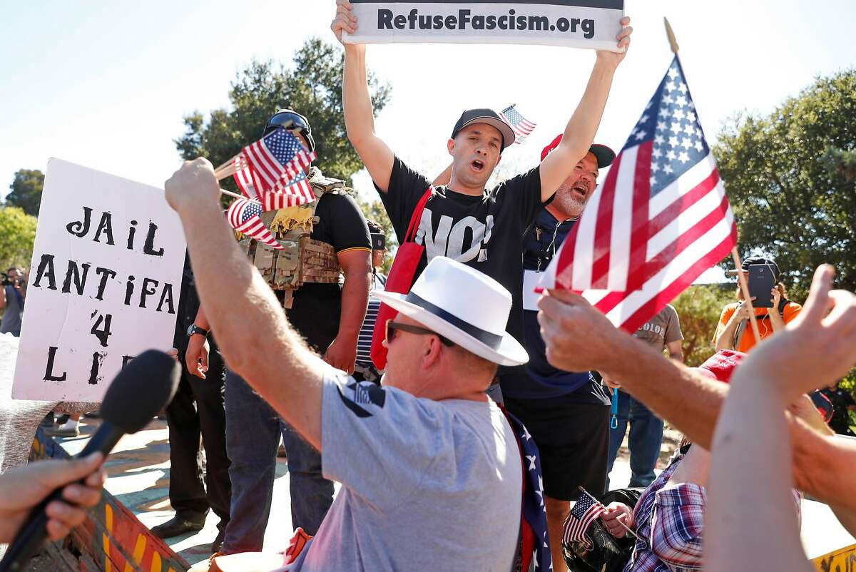 RefuseFascism.org's Rafael Kadaris is covered in American flags as he tries to interrupt a gathering of right wing activists in People's Park in Berkeley, Calif., on Tuesday, September 26, 2017. Shortly after, Kadaris was allowed to speak and share his views with the crowd.