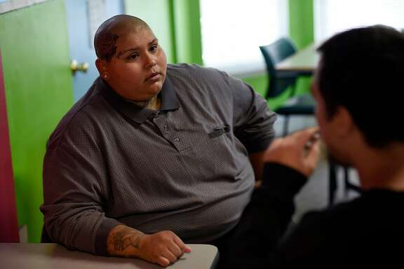 Case manager Desarie Abeyta, a former homeless youth herself who went through the transitional housing program at the Bill Wilson Center, works with a homeless youth at the Bill Wilson Center's Drop-in Center in San Jose, Calif., on Tuesday September 26, 2017.