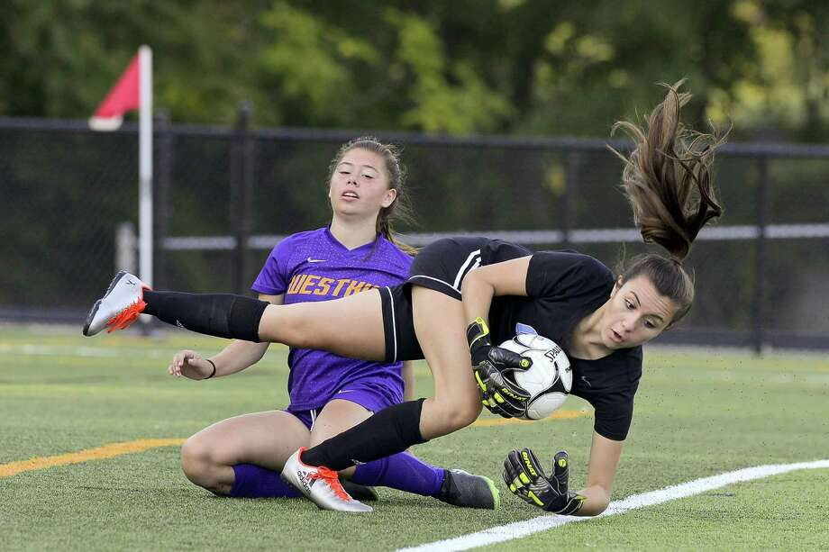 Westhill's Amy Orellana Barrientos collides with Trinity goalie Laura Cosentino in FCIAC girls soccer play at Gaglio Field in Stamford on Tuesday. Westhill defeated Trinity, 4-1. Photo: Matthew Brown / Hearst Connecticut Media / Stamford Advocate