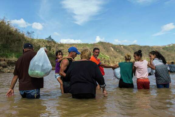 A family crosses a river in Morovis, Puerto Rico. Residents of the San Lorenzo neighborhood can't access their houses because Hurricane Maria destroyed the bridge that connects them with the main access road.