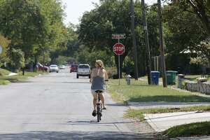 A cyclist rides along Vollum Avenue in the Monticello Park Historic District.