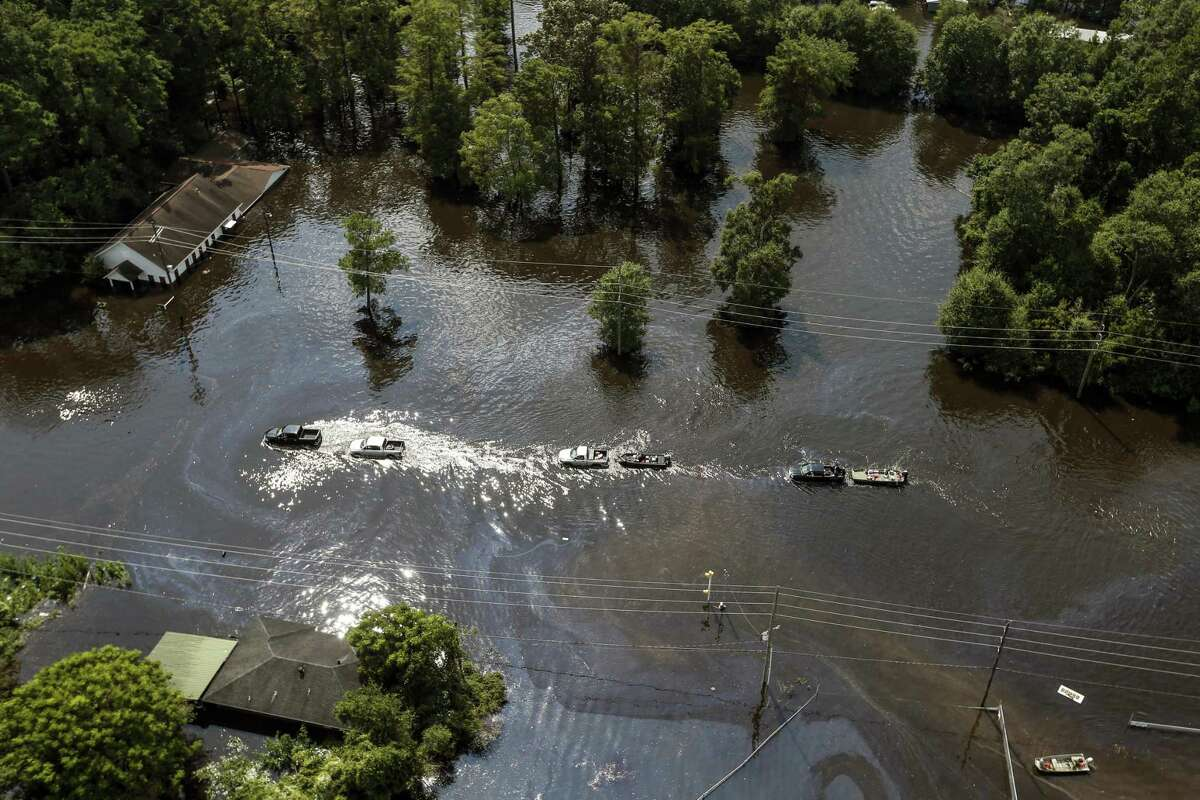 A line of vehicles roll through floodwaters of Tropical Storm Harvey on Friday, Sept. 1, 2017, in Vidor, Texas. (Brett Coomer/Houston Chronicle via AP)
