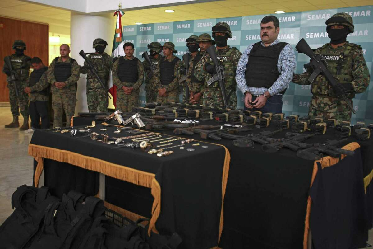 """Mexican Navy marines flank a top leader of the Gulf drug cartel, Jorge Eduardo Costilla Sanchez, known as """"El Coss,"""" second from right, as he is presented to the media along with other men dressed in military fatigues believed to be Costilla's bodyguards, at the Mexican Navy's Center for Advanced Naval Studies in Mexico City in September 2012. Costilla has pleaded guilty to conspiracy drug charges and assault, federal authorities said Tuesday."""