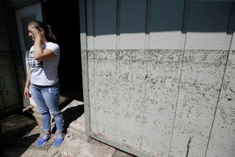 Kanani Hoover stands at the back door  where the watermark is shown on her flooded Bear Creek Village home, which sits on the north edge of the Addicks Reservoir. Photo: Melissa Phillip, Houston Chronicle / © 2017 Houston Chronicle
