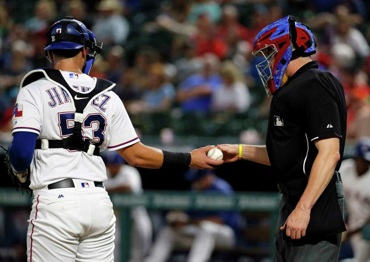 Texas Rangers catcher A.J. Jimenez (53) takes a new ball from home plate umpire Carlos Torres who wore a Rangers mask during the baseball game against the Houston Astros on Tuesday, Sept. 26, 2017, in Arlington, Texas. (AP Photo/Tony Gutierrez)