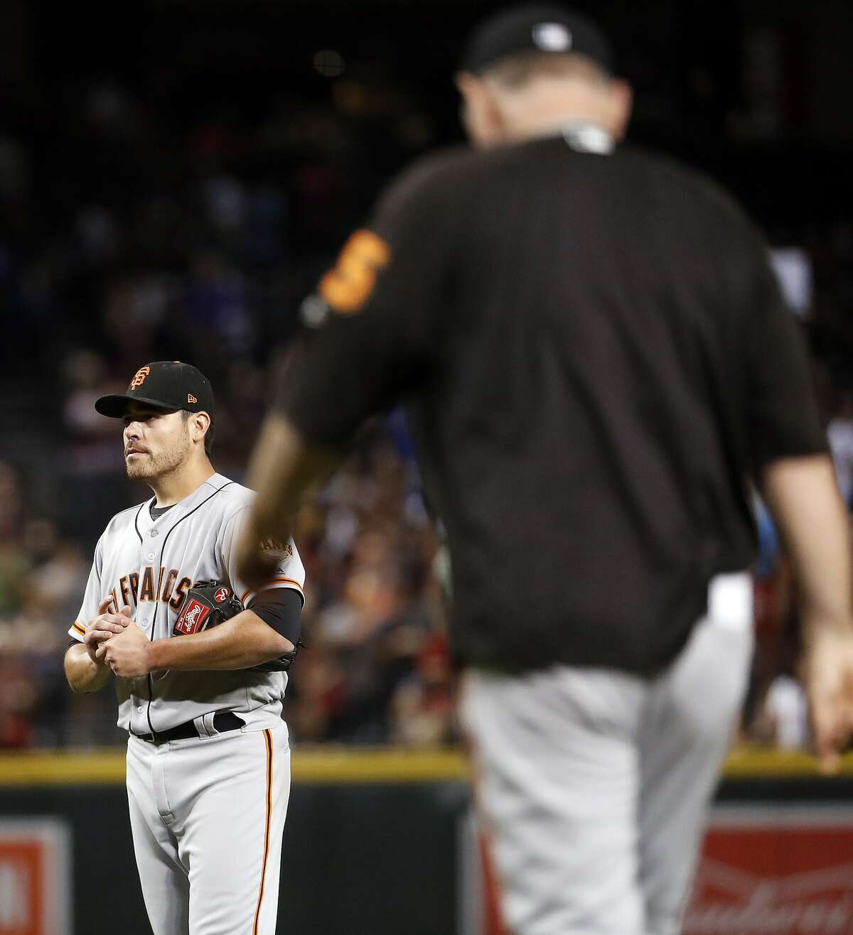San Francisco Giants starting pitcher Matt Moore waits as manager Bruce Bochy heads out to remove Moore, who had given up a grand slam to the Arizona Diamondbacks during the second inning of a baseball game, Tuesday, Sept. 26, 2017, in Phoenix. (AP Photo/Matt York)