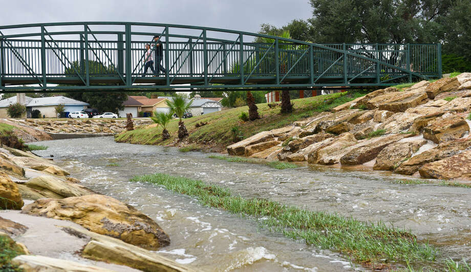 A pair of Laredoans walk on a bridge over Zacate Creek near Blas Castañeda park on Sept. 26, 2017 after rainfall filled the creek with more water than usual. Photo: Danny Zaragoza/Laredo Morning Times