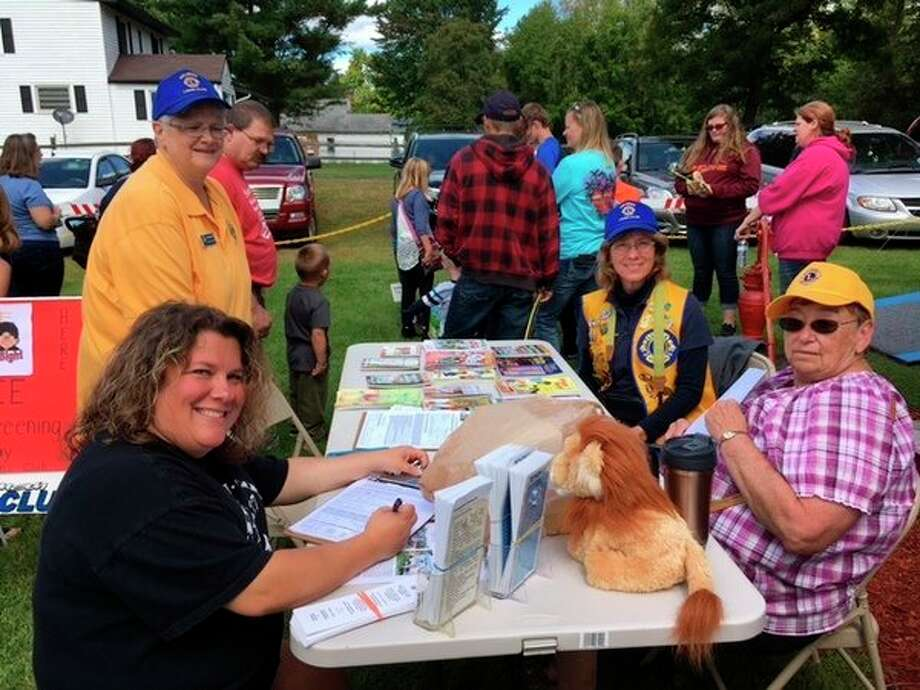 Lions Lynn Brugger, Ann Roeseler and Wendy Gross workwith mom Jodie King, who signs permission papers for her kids to have their eyes screened with a special camera during a vision screening offered by the Coleman Lions Club. (Photo provided)