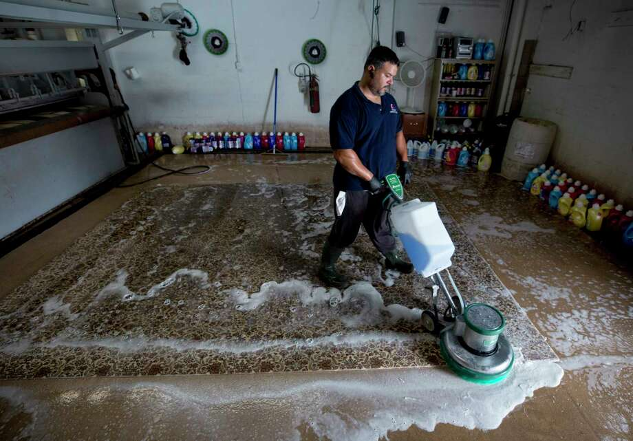 Diego Morales washes a rug that was flooded in Hurricane Harvey inside Bagdad Oriental Rugs Tuesday, Sept. 26, 2017, in Houston. ( Godofredo A. Vasquez / Houston Chronicle ) Photo: Godofredo A. Vasquez, Houston Chronicle / Godofredo A. Vasquez