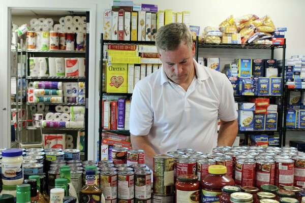 Jeff Turner, one of the organizers for Wilton Kiwanis Club's quarterly food drives, stocks the Wilton Food Pantry with donations from Sept. 22-24, 2017.
