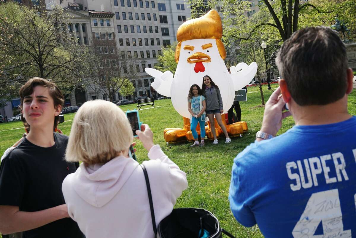 """People pose with an inflatable """"Trump Chicken"""" in downtown Washington, DC on April 14, 2017 ahead of the """"Tax March"""". The """"chicken"""" is touring the area to promote the march, which aims to pressure US President Donald Trump into releasing his tax records. / AFP PHOTO / MANDEL NGAN (Photo credit should read MANDEL NGAN/AFP/Getty Images)"""
