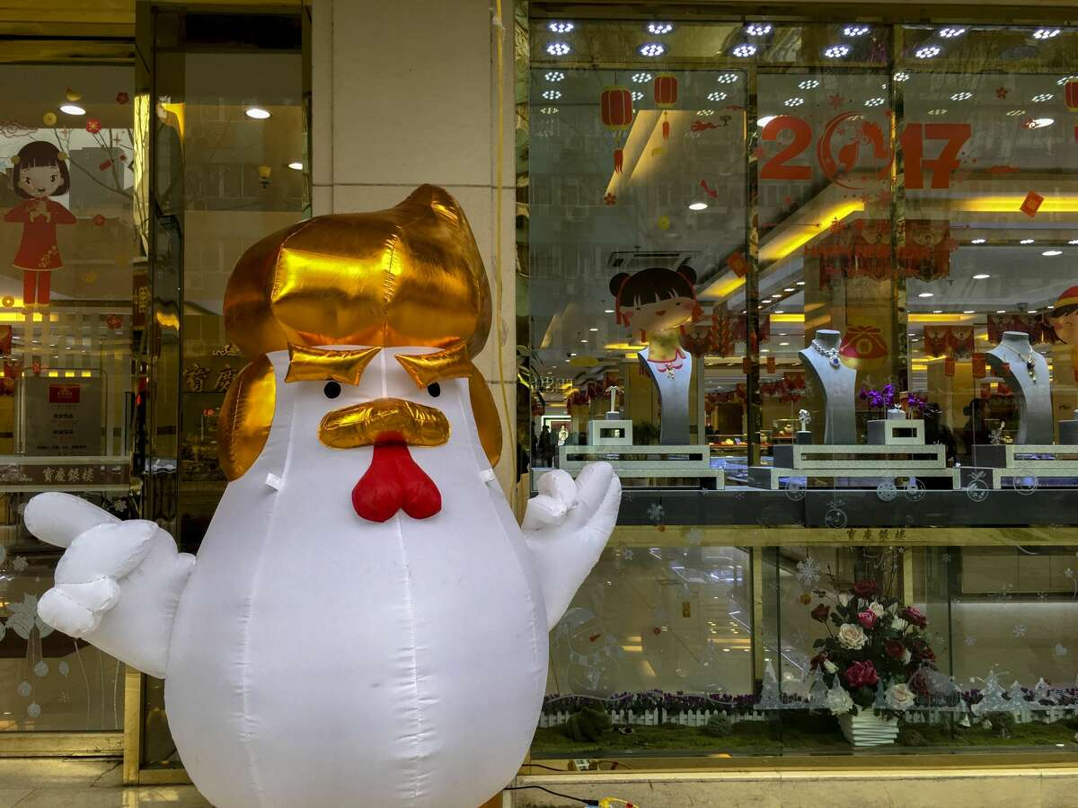 NANJING, CHINA - 2017/01/31: An inflatable chicken with a Donald Trump hairstyle and hand gestures, stands outside a gold shop to attract customers. (Photo by Zhang Peng/LightRocket via Getty Images)
