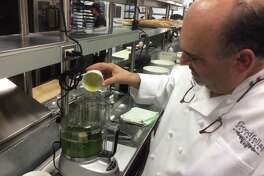 Chef Gerry Iannaccone adds olive oil to the blender as he prepares pesto for swordfish with pesto over pasta at Goodfellas Restaurant in New Haven.
