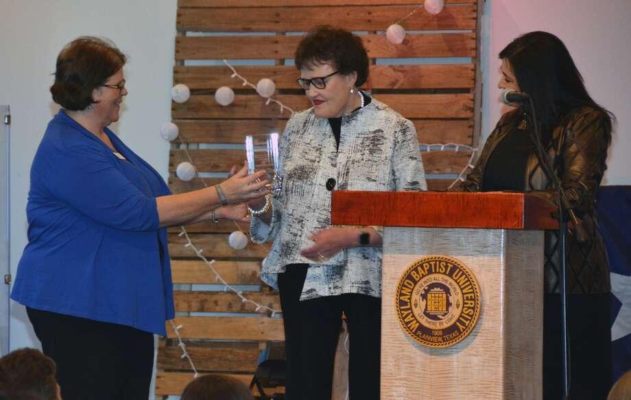 Dr. Glenda Payas is presented the Distinguished Benefactor Award by Wayland Alumni Director Teresa Young.