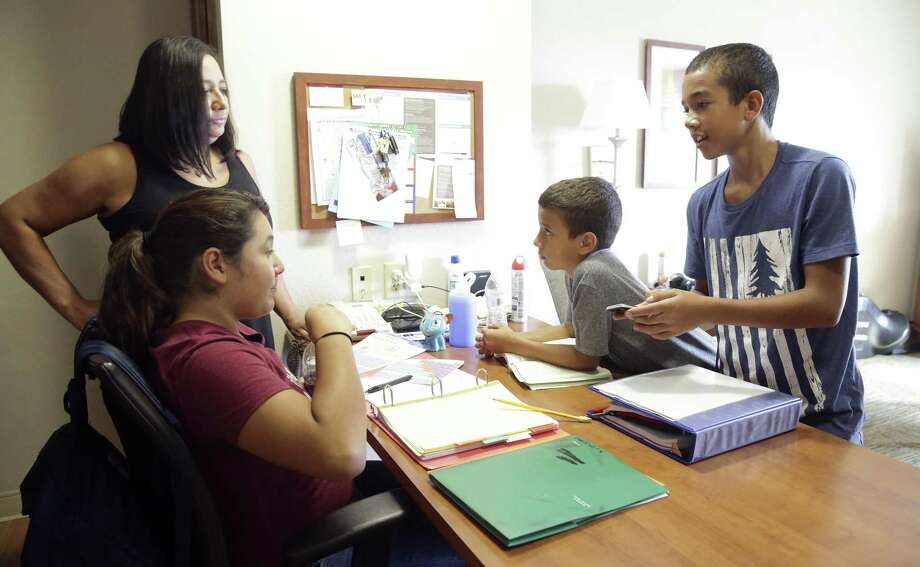 Three sixth graders get together to do homework with Marta Moody as Lori Bailey (Marts's daughter) manages her children, just home from school, at an apartment in Northwest in San Antonio on September 19, 2017. Kids are from left, Dakota Rimirez, Adriel Bailey and Gaige Bailey. Photo: Tom Reel, Staff / San Antonio Express-News / 2017 SAN ANTONIO EXPRESS-NEWS