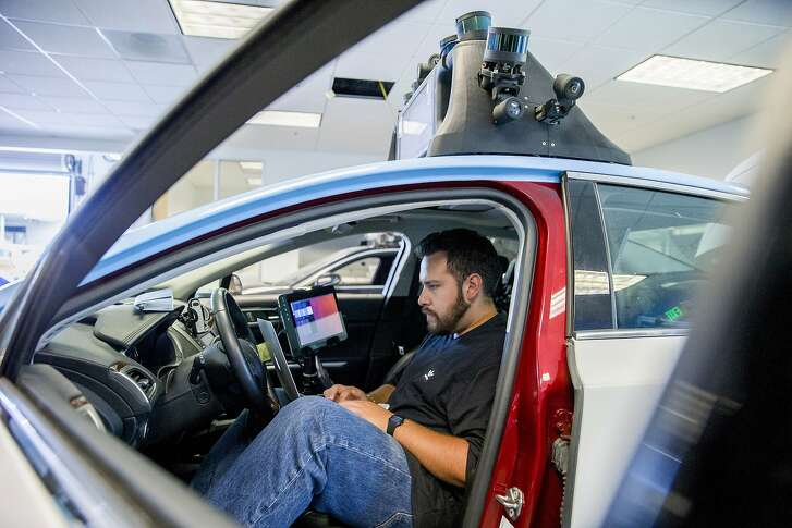 Martin Vega checks the software of the self driving vehicle at drive.ai on Wednesday, Aug. 9, 2017, in Mountain View, Calif. Drive.ai is a Silicon Valley startup that's creating artificial intelligence software for autonomous vehicles.