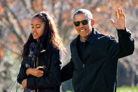 WASHINGTON, DC - JANUARY 3: (AFP OUT) U.S. President Barack Obama waves to the assembled press as he walks with his daughter Malia on his family's return to the South Lawn of the White House January 3, 2016 in Washington, DC.