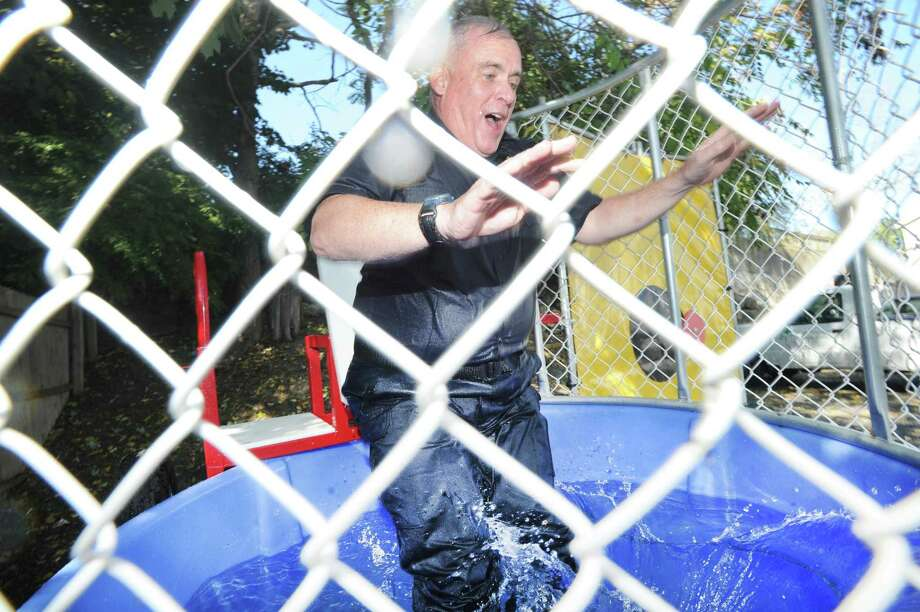 "Greenwich Police Chief James Heavey gets dropped into the water of a dunk-tank after one of his officers made a throw that hit the triggering-device during the ""Thank a Cop"" law enforcement appreciation day event at Joey B's Chili Hub in the Cos Cob section of Greenwich, Conn., Wednesday, Sept. 27, 2017. Donations and funds raised during the event went to the college scholarship fund for the families of Greenwich law enforcement. Photo: Bob Luckey Jr. / Hearst Connecticut Media / Greenwich Time"
