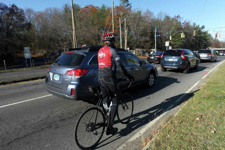 FILE - A bicyclist waits at a red light with traffic on High Ridge Road. Photo: Hearst Connecticut Media File Photo / Stamford Advocate