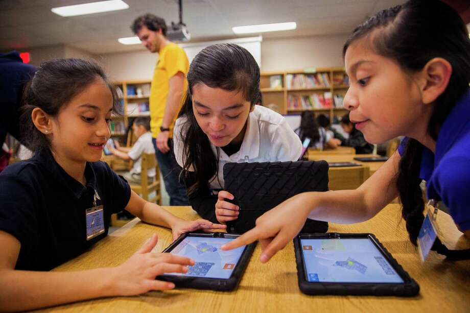"Fourth graders Ciclady Martinez, 9, (from left) Paulina Perales, 9, and Yasmin Lepe, 9, play on an App called ""Lightbot Hour,"" that teaches introductory coding concepts Monday Dec. 7, 2015 during an Hour of Code at Walzem Elementary School. In honor of Computer Science Education Week, students around the world will  participate this week in the Hour of Code. Photo: Julysa Sosa, Freelancer / For The Express-News / San Antonio Express-News"