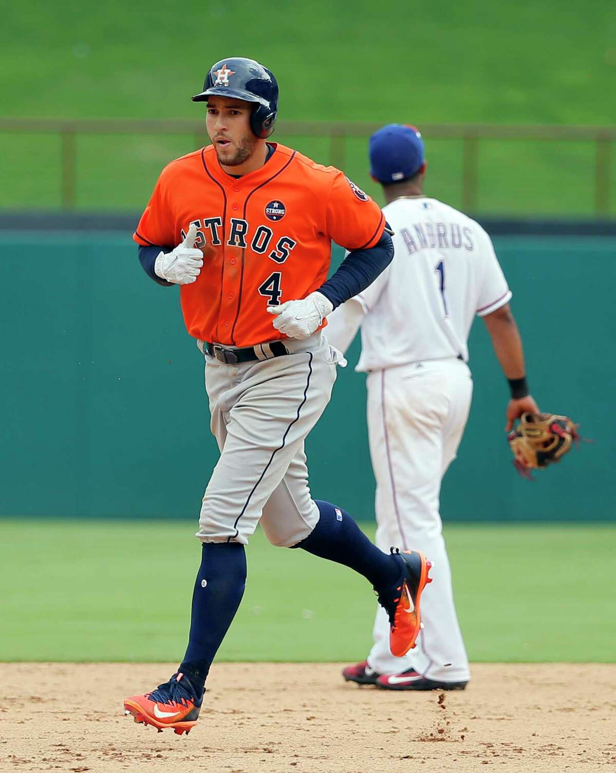 Houston Astros' George Springer (4) rounds the bases past Texas Rangers shortstop Elvis Andrus after hitting a grand slam off Rangers relief pitcher Tony Barnette in the sixth inning of a baseball game, Wednesday, Sept. 27, 2017, in Arlington, Texas. (AP Photo/Tony Gutierrez)