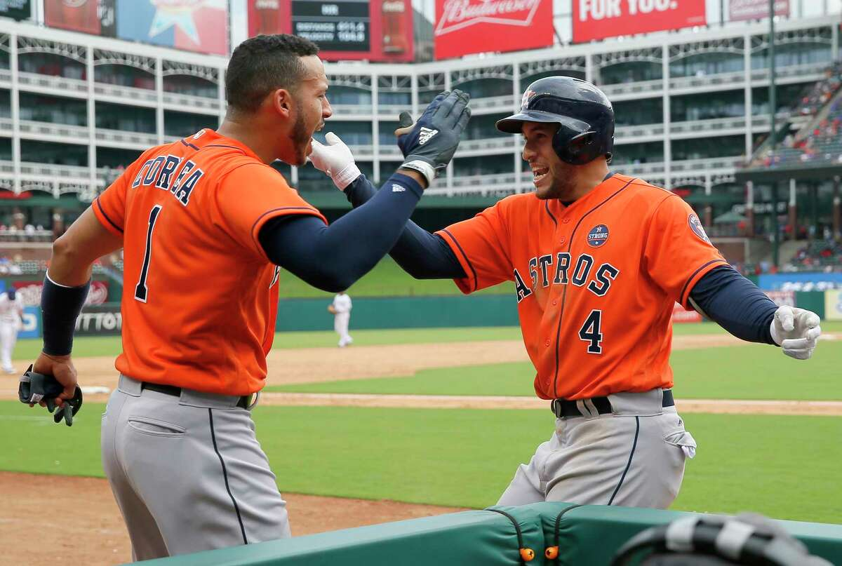 Houston Astros' Carlos Correa (1) and George Springer (4) celebrate Springer's grand slam in the sixth inning of a baseball game against the Texas Rangers on Wednesday, Sept. 27, 2017, in Arlington, Texas. (AP Photo/Tony Gutierrez)