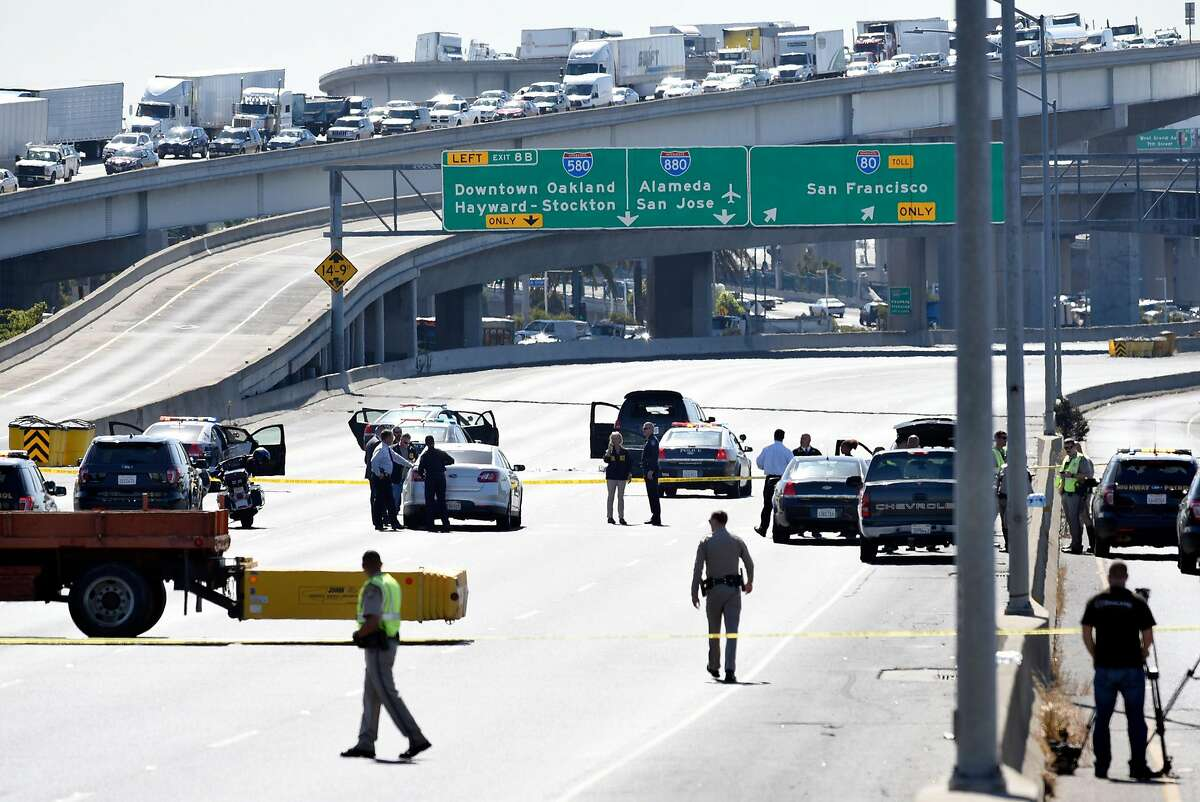Authorities investigate the scene following a police shooting which occurred on the Westbound lanes of Interstate 80 in Emeryville, Calif. on Wednesday September 27, 2017. The individual shot by the authorities was a fleeing murder suspect who exited his black SUV (center) holding a weapon.
